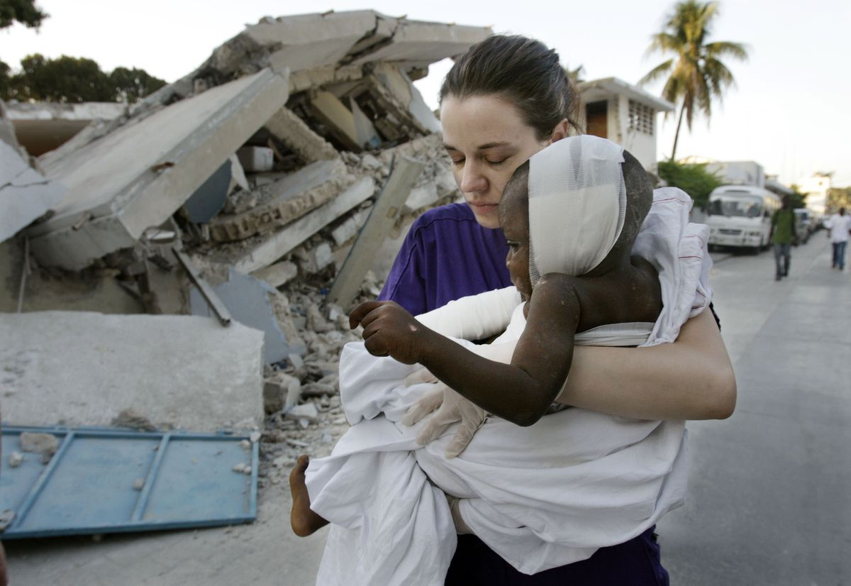 """Elizabeth """"Liz"""" Howell carries 4-year-old Oresto Oclor to a hospital for surgery in Port-au-Prince, Haiti."""