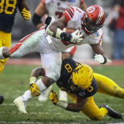 Utah Utes running back Zack Moss (2) is knocked off his feet by West Virginia Mountaineers safety Kyzir White (8) at the Zaxby's Heart of Dallas Bowl between the Utah Utes and the West Virginia Mountaineers in Dallas Texas on Tuesday, Dec. 26, 2017.
