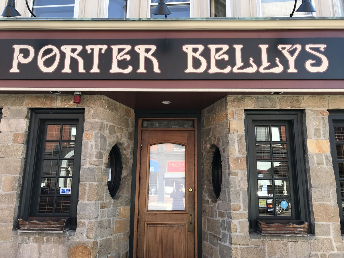 Light brick exterior of a bar with black signage that readers Porter Belly's in gold on black