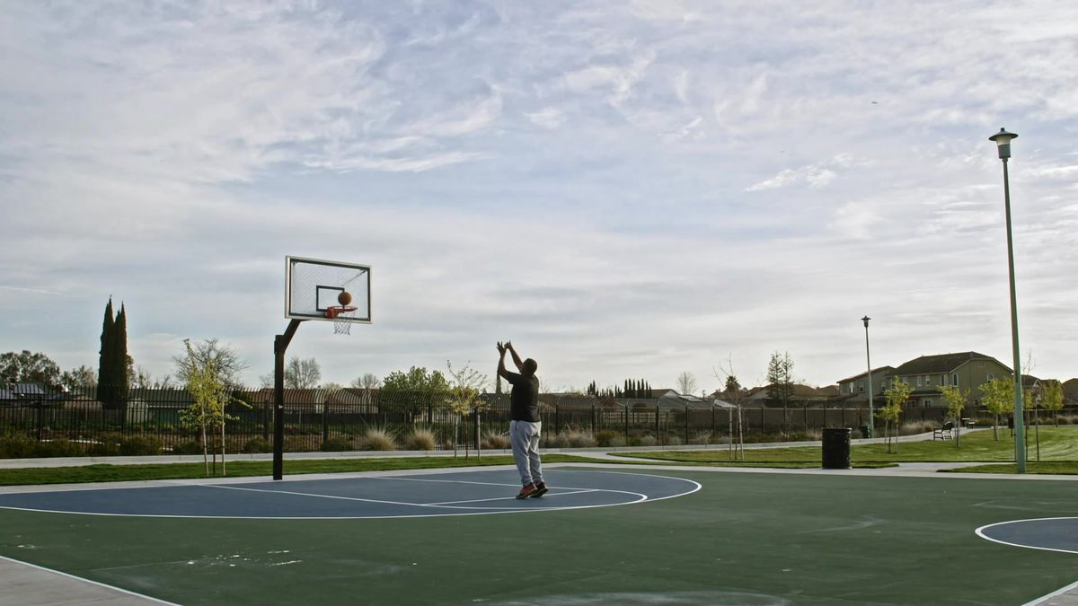 A person alone on a suburban park's basketball court, shooting a basket.