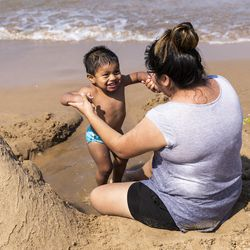 Yoselin Cuatlatl, 22, of Hammond, Indiana, plays with her 1-year-old son Adam Cortes near the family's sand castle at 63rd Street Beach on the South Side, Wednesday afternoon, July 24, 2019.