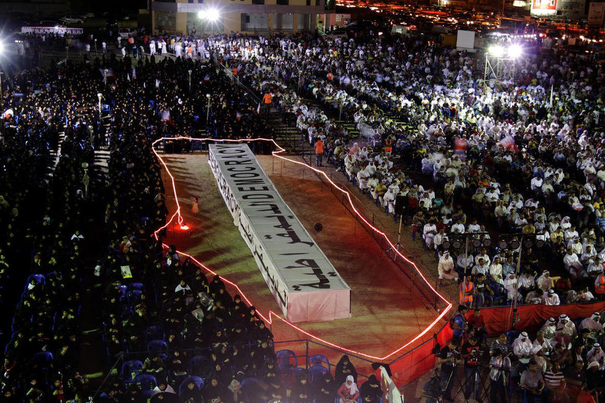 """Pro-democracy protesters listen to speakers at a rally organized by opposition groups while seated around a stage shaped like the boundaries of Bahrain and containing a mock casket with the word """"democracy"""" in English and Arabic. Bahrain says it has charg"""