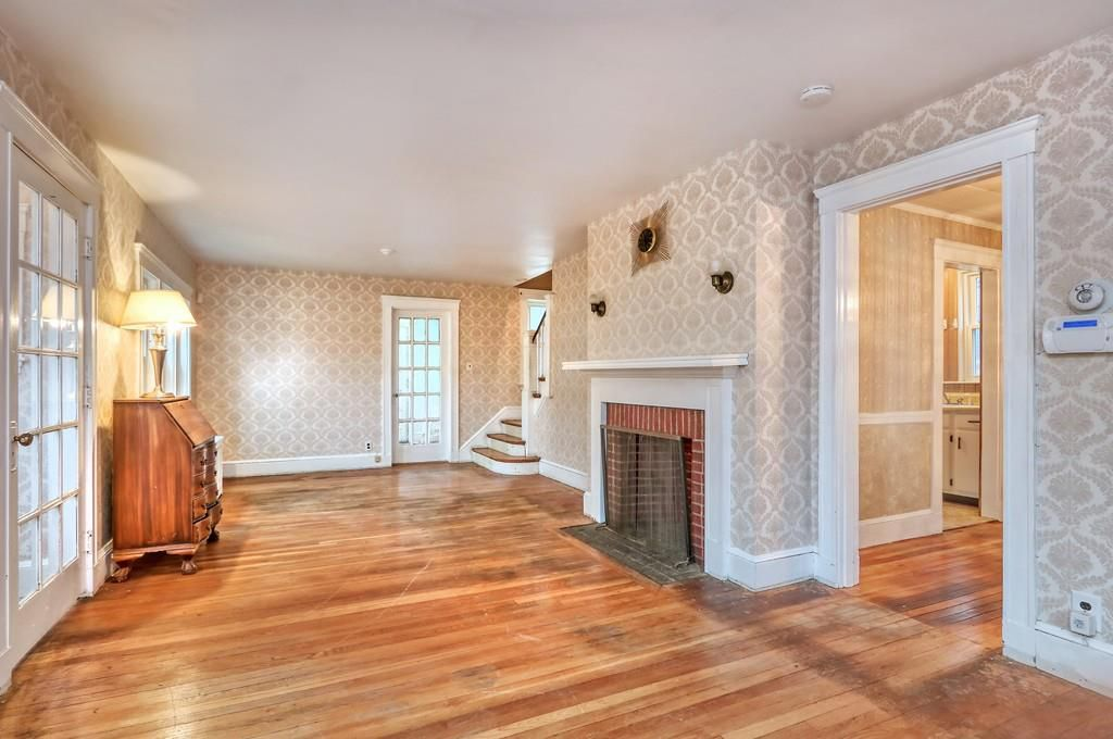 A largely empty and large living room with a fireplace and stairs leading up from the end of it.