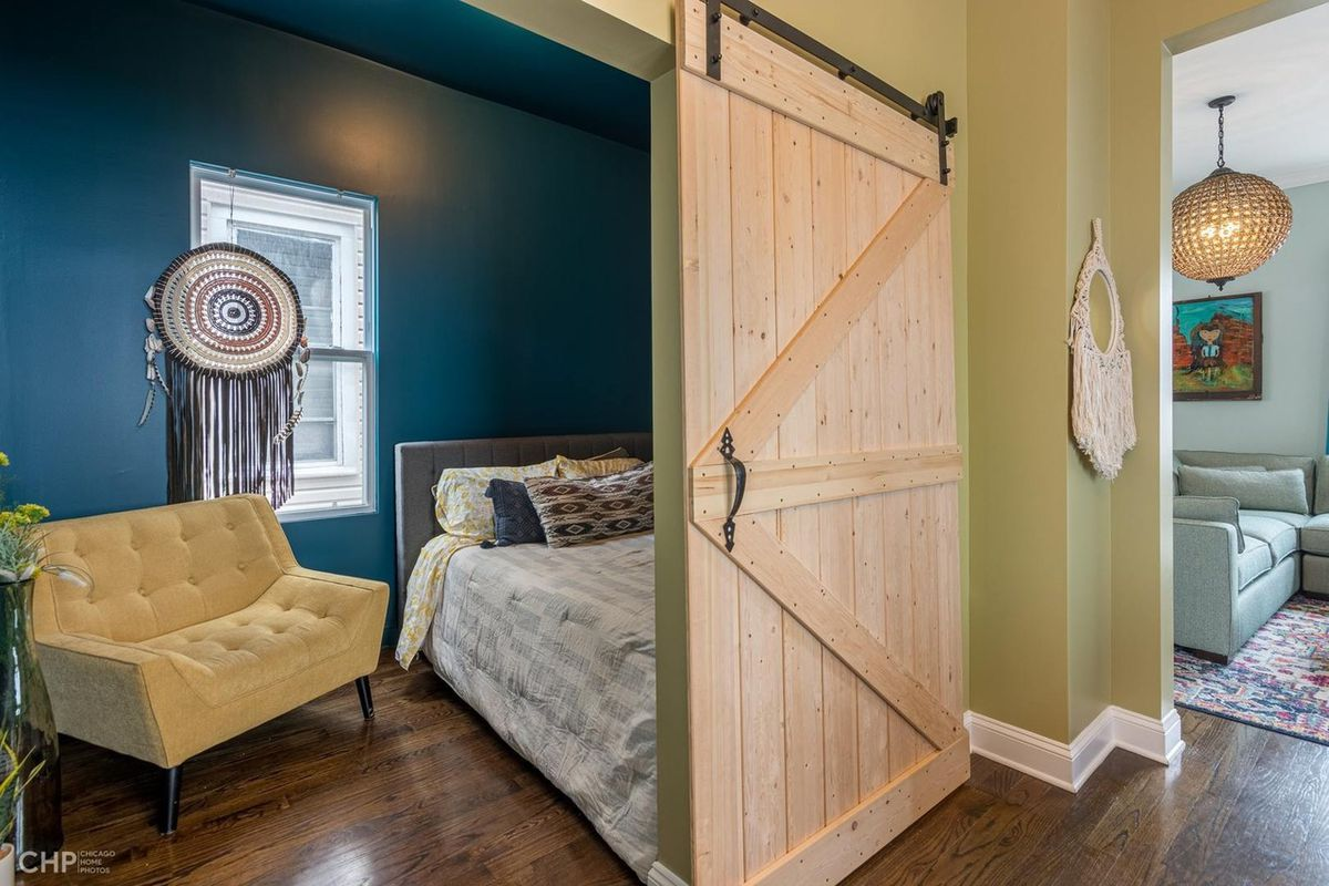 A sliding barn door reveals a bedroom with a blue wall and a cream colored chair.