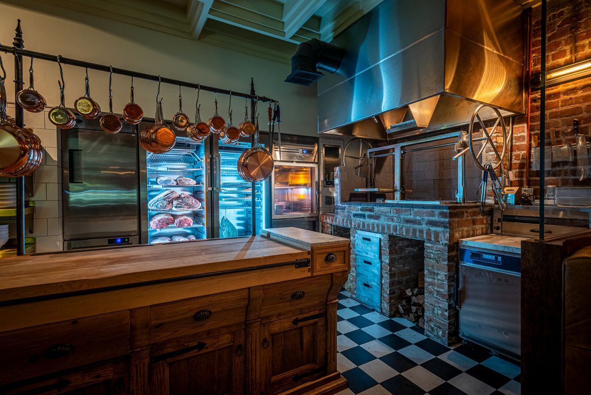 Open kitchen with hanging copper pots, open wooden grill and illuminated meat boxes.