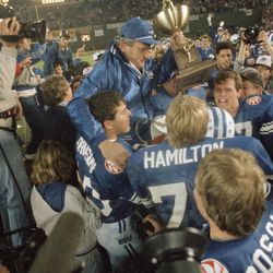 Brigham Young University football coach LaVell Edwards holds the trophy as he is carried off the field following BYU's 24-17 victory over the University of Michigan in the Holiday Bowl on Dec. 22, 1984, in San Diego.