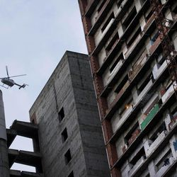 A helicopter of the National Bolivarian Police flights over a building occupied by squatters allegedly looking for the abductors of Costa Rican diplomat Guillermo Cholele in Caracas, Venezuela, Monday April 9, 2012. Cholele was kidnapped on Sunday in Venezuela and his abductors have demanded a ransom, Costa Rican officials said Monday.
