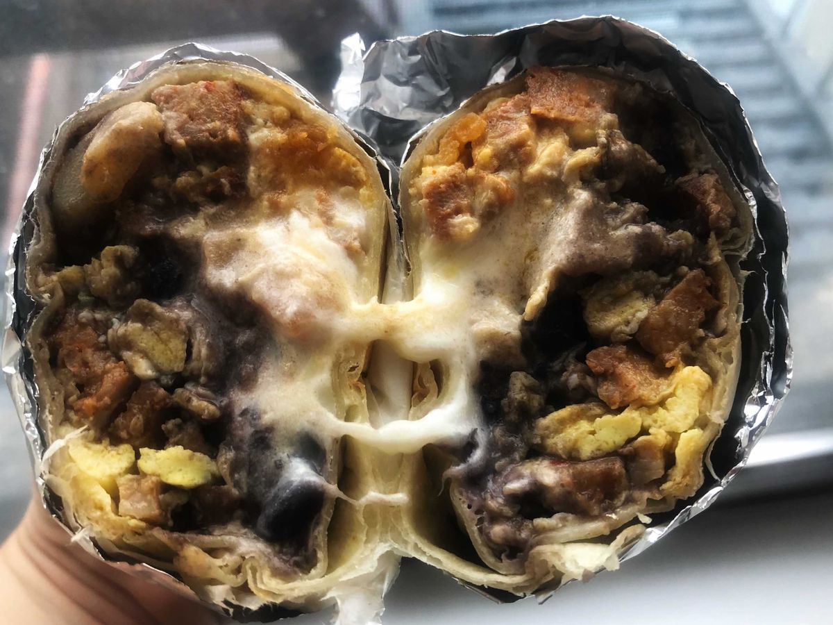 A foil-wrapped breakfast burrito cut open and the two halves placed side by side to show the insides with potatoes, cheese, egg, chorizo, and beans.