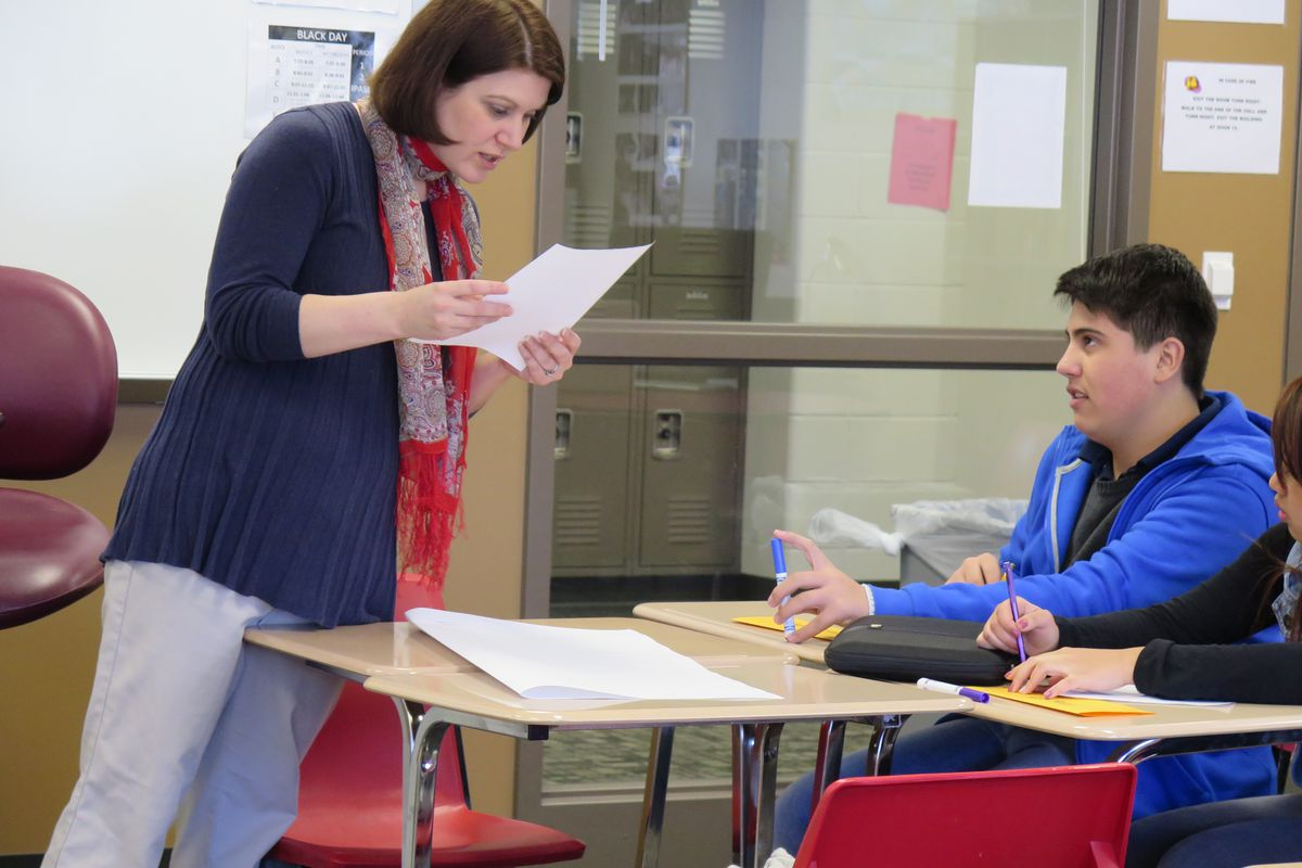 Amy Peddie, an English as a new language teacher at Southport High School, helps a student on an assignment in her class.