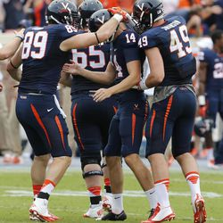 Virginia kicker Ian Frye (14) is swarmed by teammates  including tight end Rob Burns (89) and Zachary Swanson (49) after kicking the game-winning field goal late in the second half of an NCAA college football game against Louisvile in Charlottesville, Va., Saturday, Sept. 13, 2014. Virginia won the game 23-21. (AP Photo/Steve Helber)