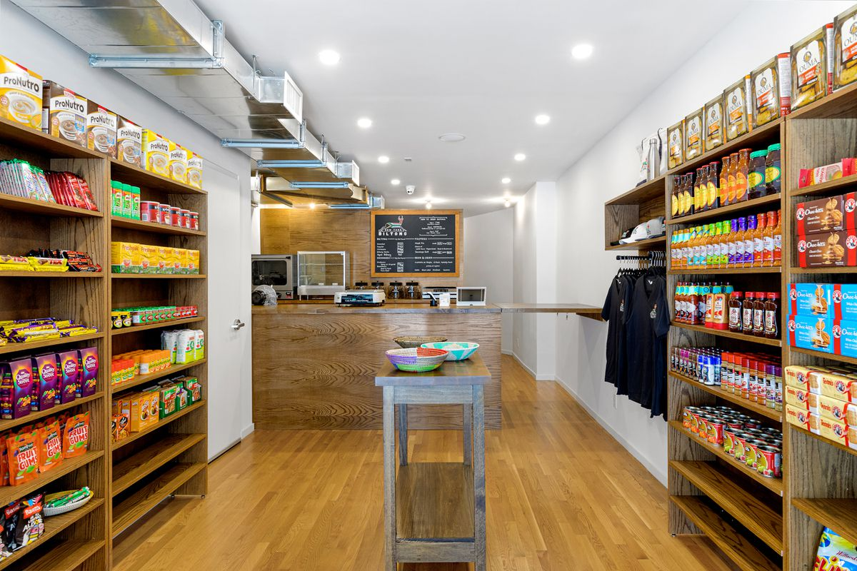 The interior of a store with a counter in the middle and shelves on either side that have different packaged foods on them