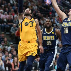 Utah Jazz guard Ricky Rubio (3) lays it up ahead of Denver Nuggets forward Kenneth Faried (35) and center Nikola Jokic (15) at Vivint Smart Home Arena in Salt Lake City on Tuesday, Nov. 28, 2017.