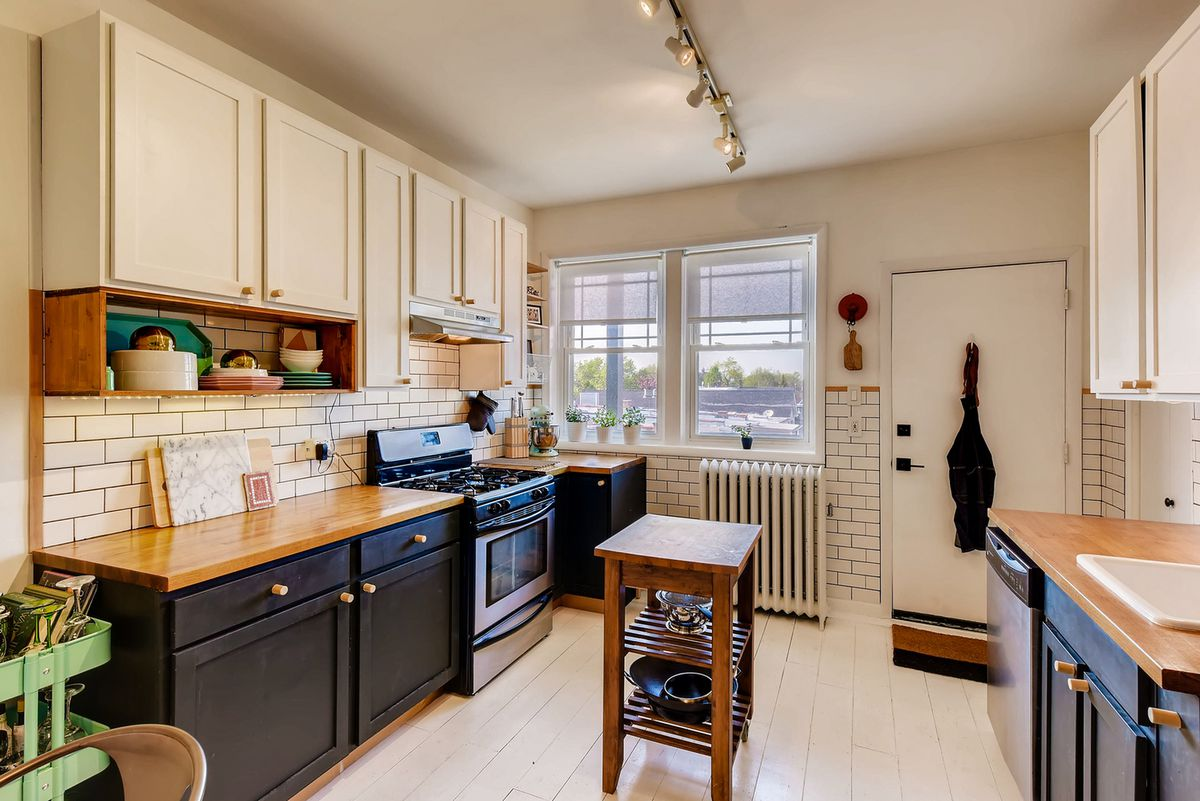 The kitchen has butcher block counters, navy cabinets down low and white cabinets up top. There is a wood floor painted white and white subway tiling.