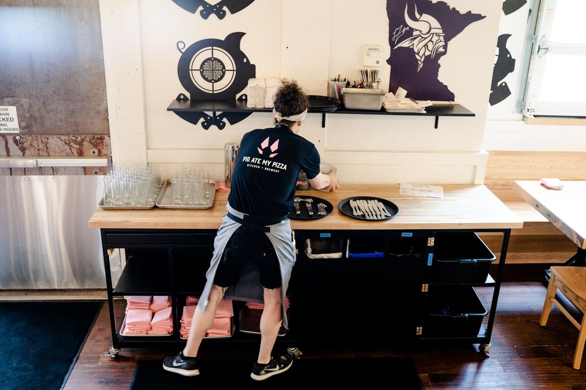 A worker in a black Pig Ate My Pizza t-shirt is working on packaging pizzas inside the restaurant during its opening last year.
