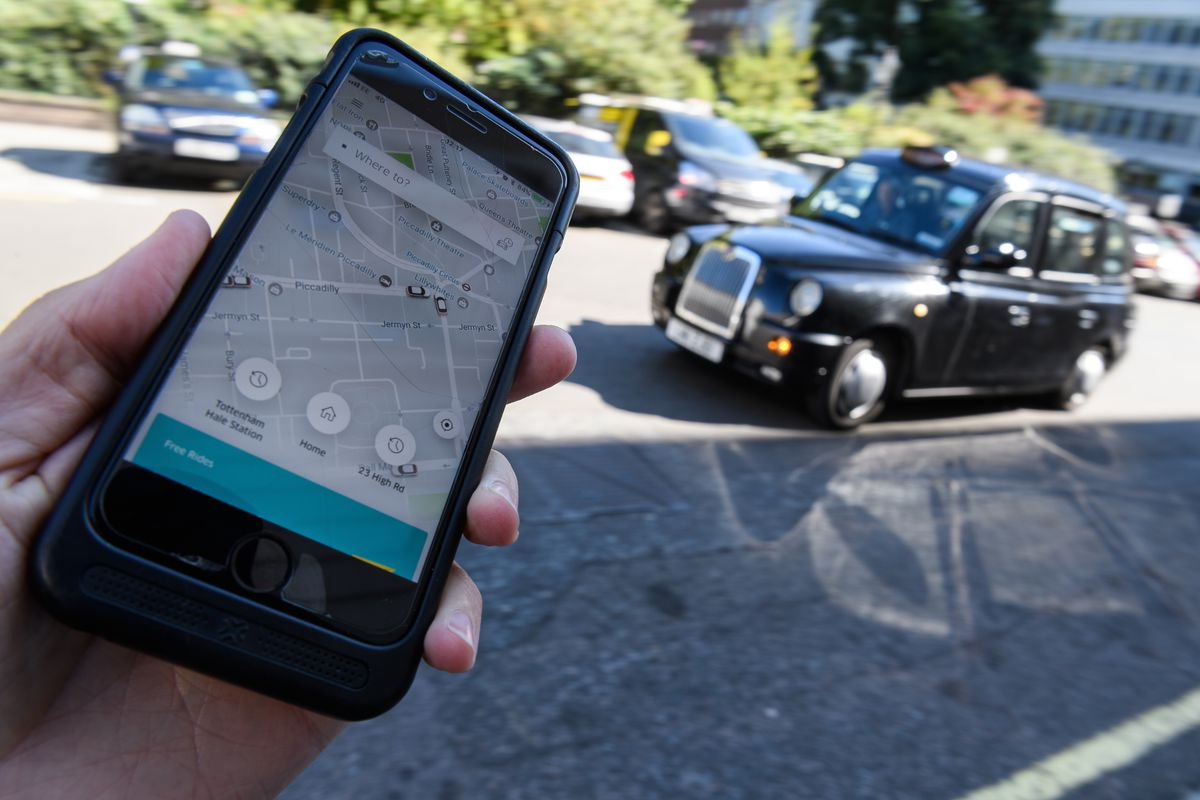 An Uber users holds out a phone showing the Uber app interface as a car drives by on a road in the background.