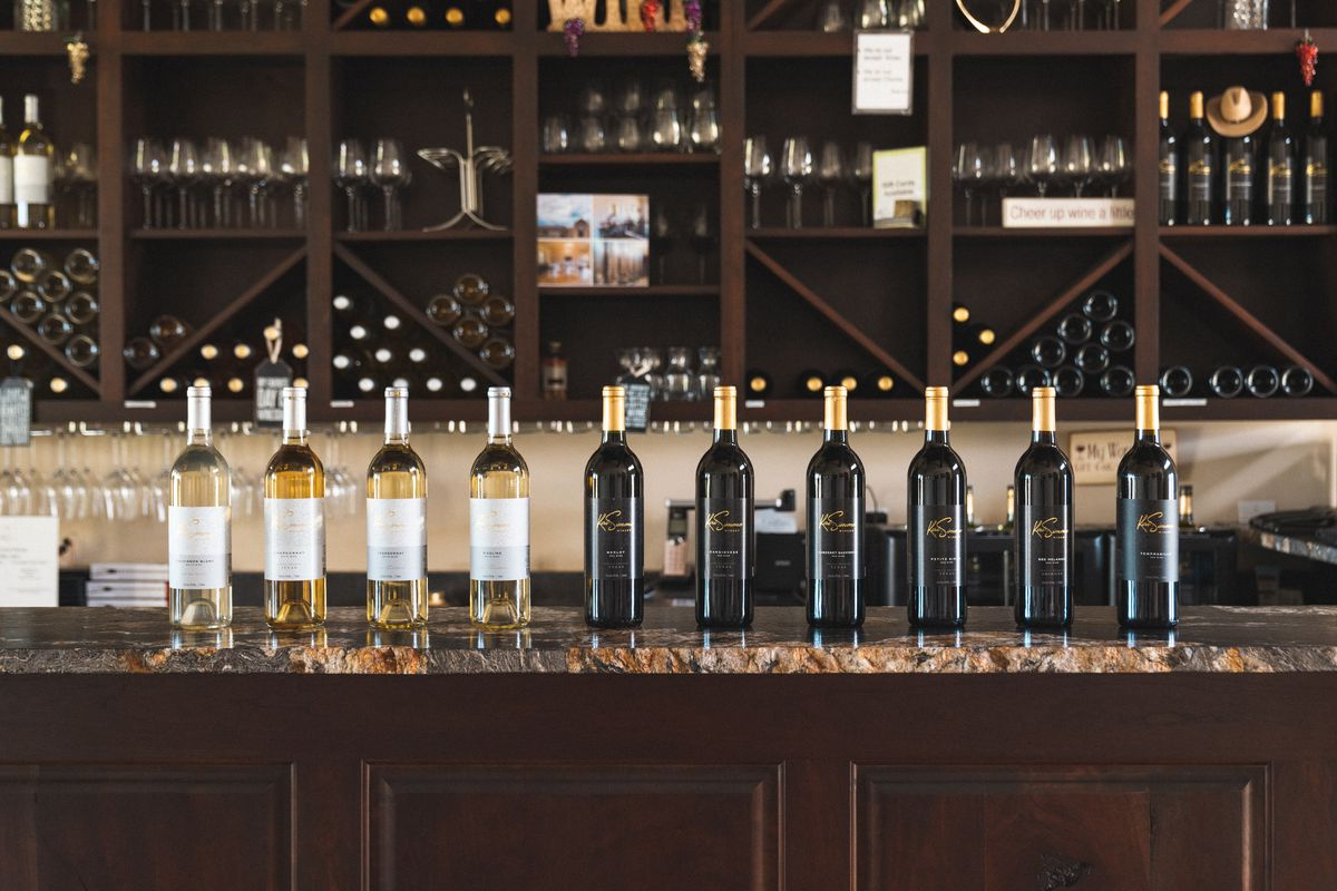 A row of wines — starting from pale yellow all the way to red — on a marble bar; in the background, shelves of wine glasses and bottles.