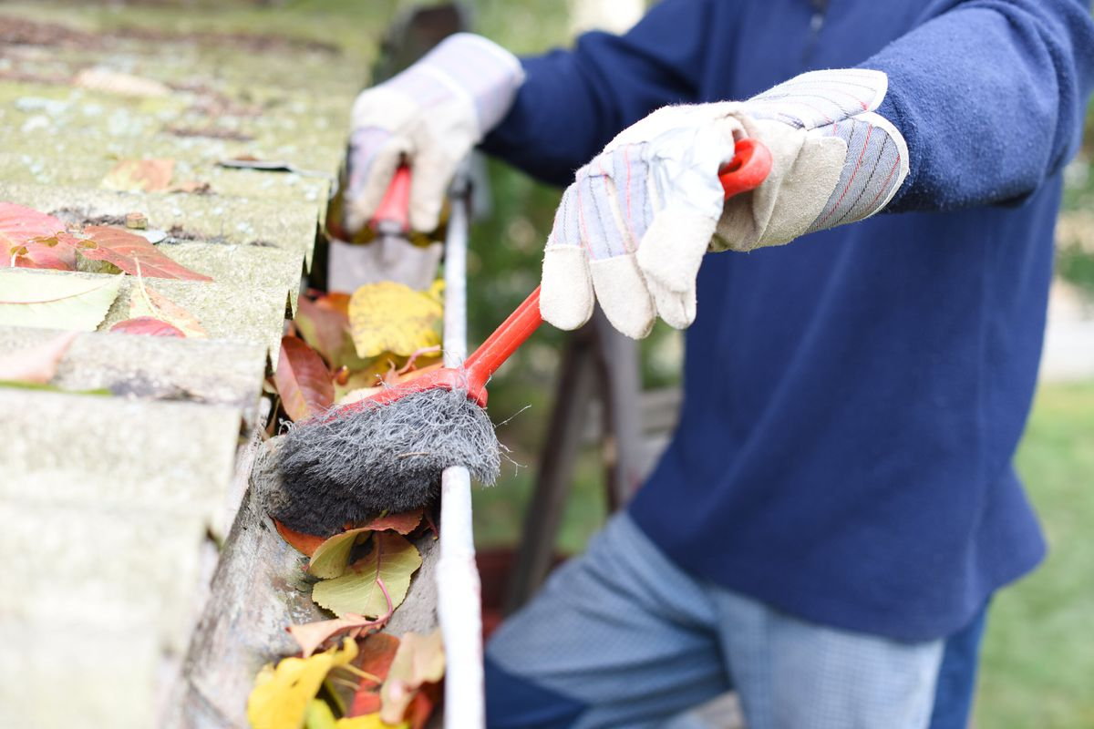 A professional wearing a navy blue shirt, blue jeans, and protective gloves uses a brush to brush out leaves from a gutter.