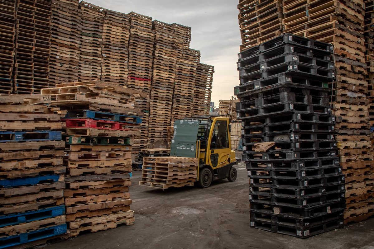 A forklift drives through a yard stacked high with pallets