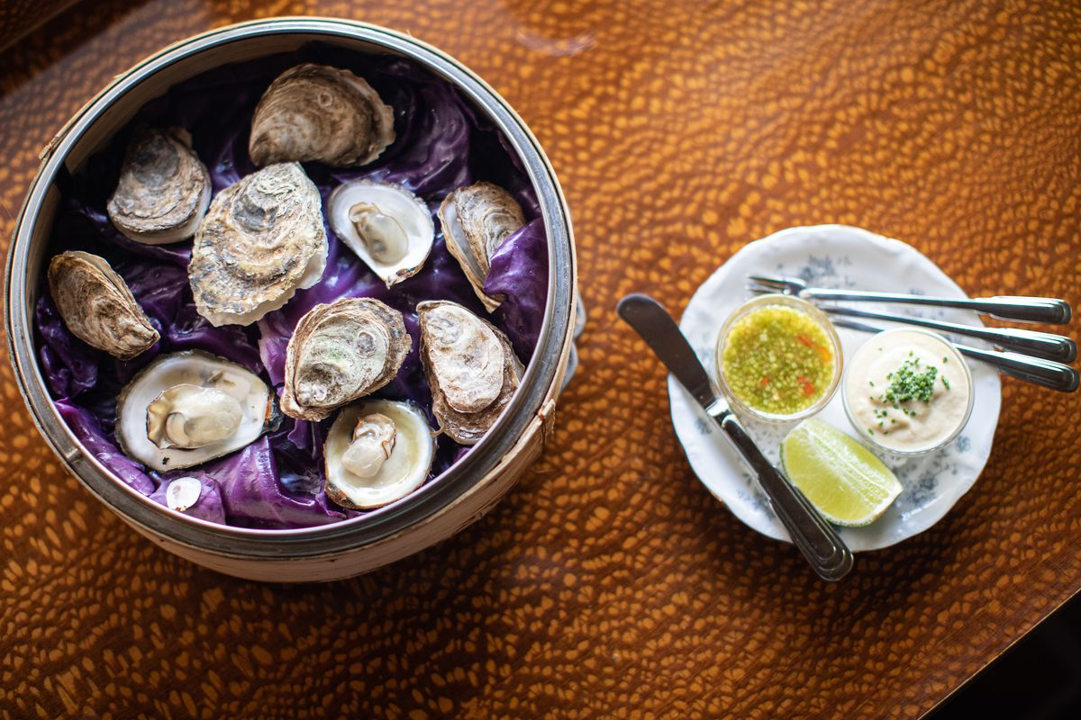 A bowl of oysters set on a plate with a purple cloth under it. A plate with a white sauce and a yellow sauce are next to it.