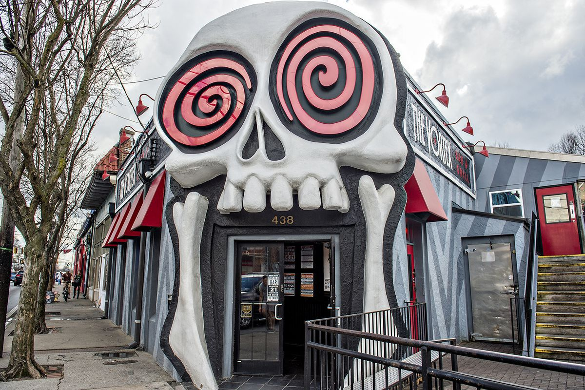 An entrance to a market place. The entrance is shaped and painted like a cartoon skull. The skull's eyes are pink and swirly.