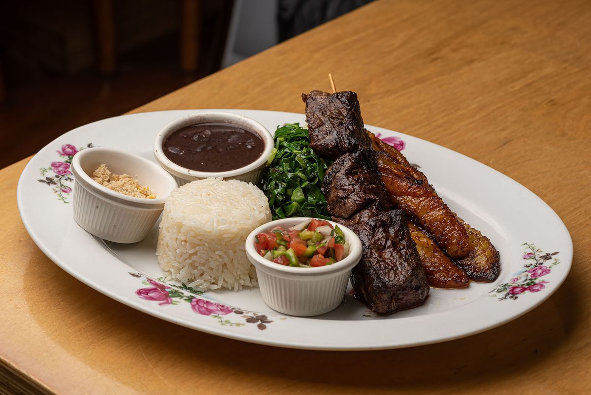 Grilled meats, rice, beans, farofa, and salsa at Wood Spoon on a flower-decorated plate.