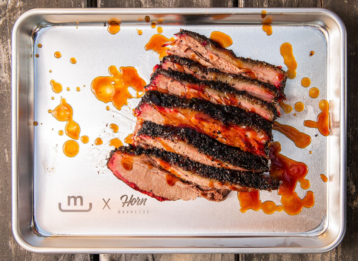 A silver tray of sliced brisket, barbecue dotted across the surface of the meat and tray like a Jackson Pollock painting