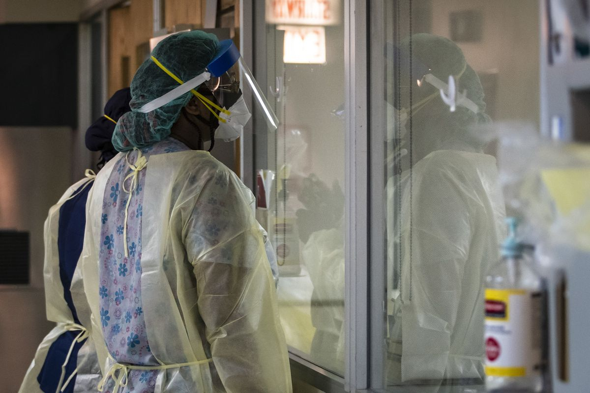 Nurses look through a window as they check on a man with COVID-19 and on a ventilator earlier this month in the Intensive Care Unit at Roseland Community Hospital on the Far South Side.
