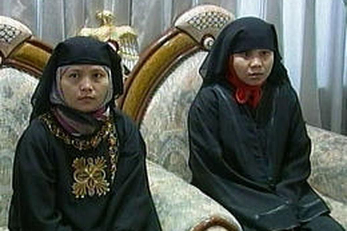 Two Indonesian women who were kidnapped in Iraq are seen on video at the United Arab Emirates embassy in Baghdad after their release by militants Monday.