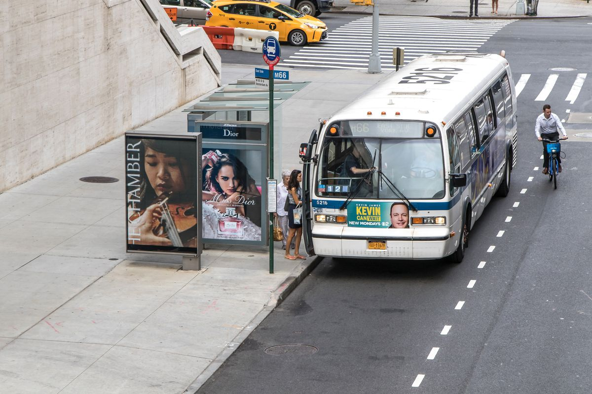 Passengers board a New York City bus at a major intersection.