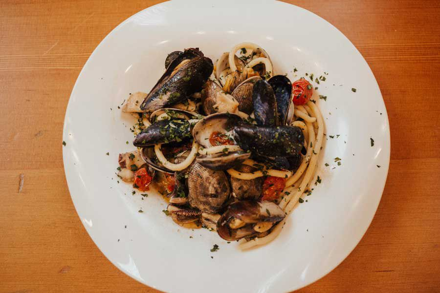 A plate of pasta with tomatoes and mussels.