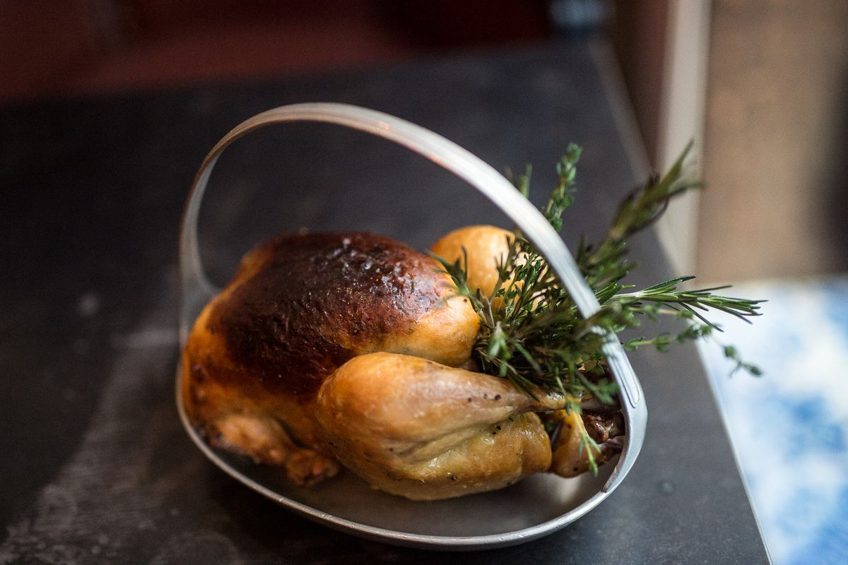 A roast chicken stuffed with herbs in a basket