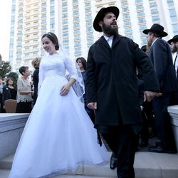 Chaya Zippel and Rabbi Mendy Cohen walk as wife and husband after their traditional Chabad Lubavitch Jewish wedding at the Grand America Hotel in Salt Lake City on Monday, Sept. 12, 2016.