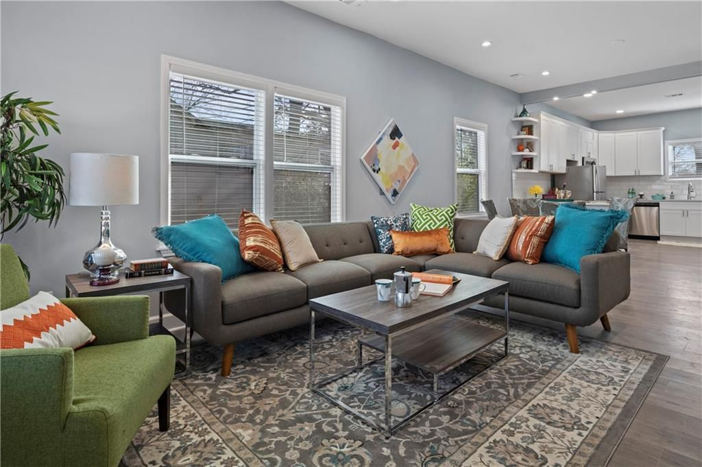 Living area with couches, a green chair, coffee table and area rug.