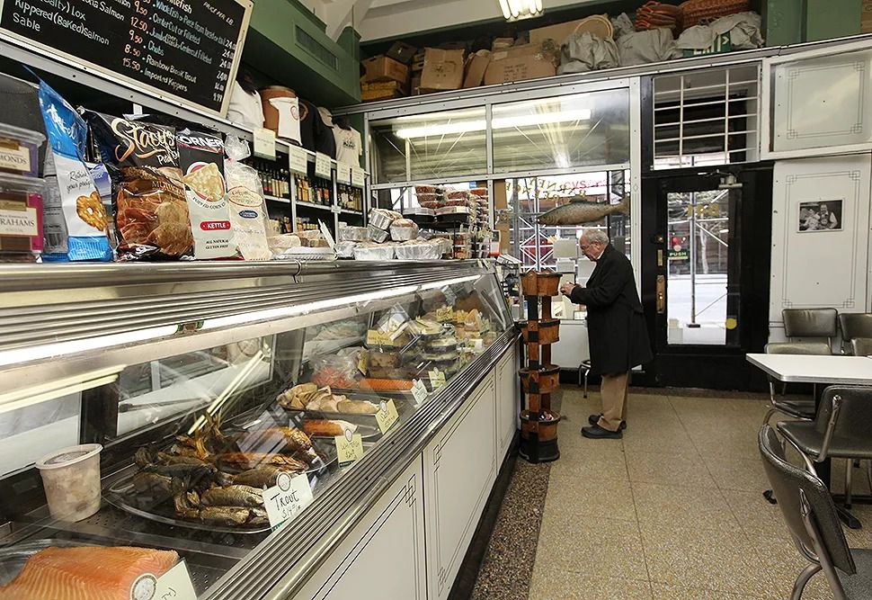 The interior of Barney Greengrass with a man waiting to order food. The refrigerated counter showcases the different meats and spreads the establishment has to offer.