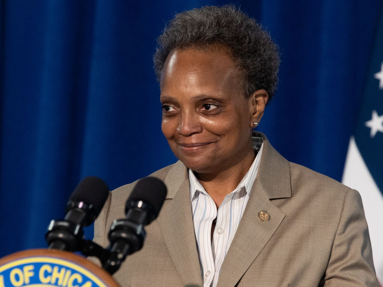 Chicago Mayor Lori Lightfoot smiles as she walks to the podium to answer questions.