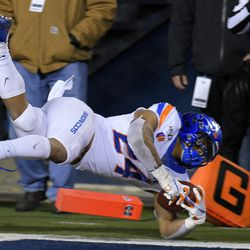 Boise State running back George Holani (24) dives into the end zone for a 5-yard touchdown against Utah State during the first half of an NCAA college football game Saturday, Nov. 23, 2019, in Logan, Utah.