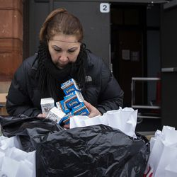 Hilda Perez, a lunchroom attendant, packs a bag of three days of free breakfast and lunch meals for students at William P. Nixon Elementary School, 2121 N. Keeler Ave., Thursday morning, March 19, 2020. All Illinois schools, including Chicago Public Schools, are closed for weeks amid fears of the coronavirus pandemic.