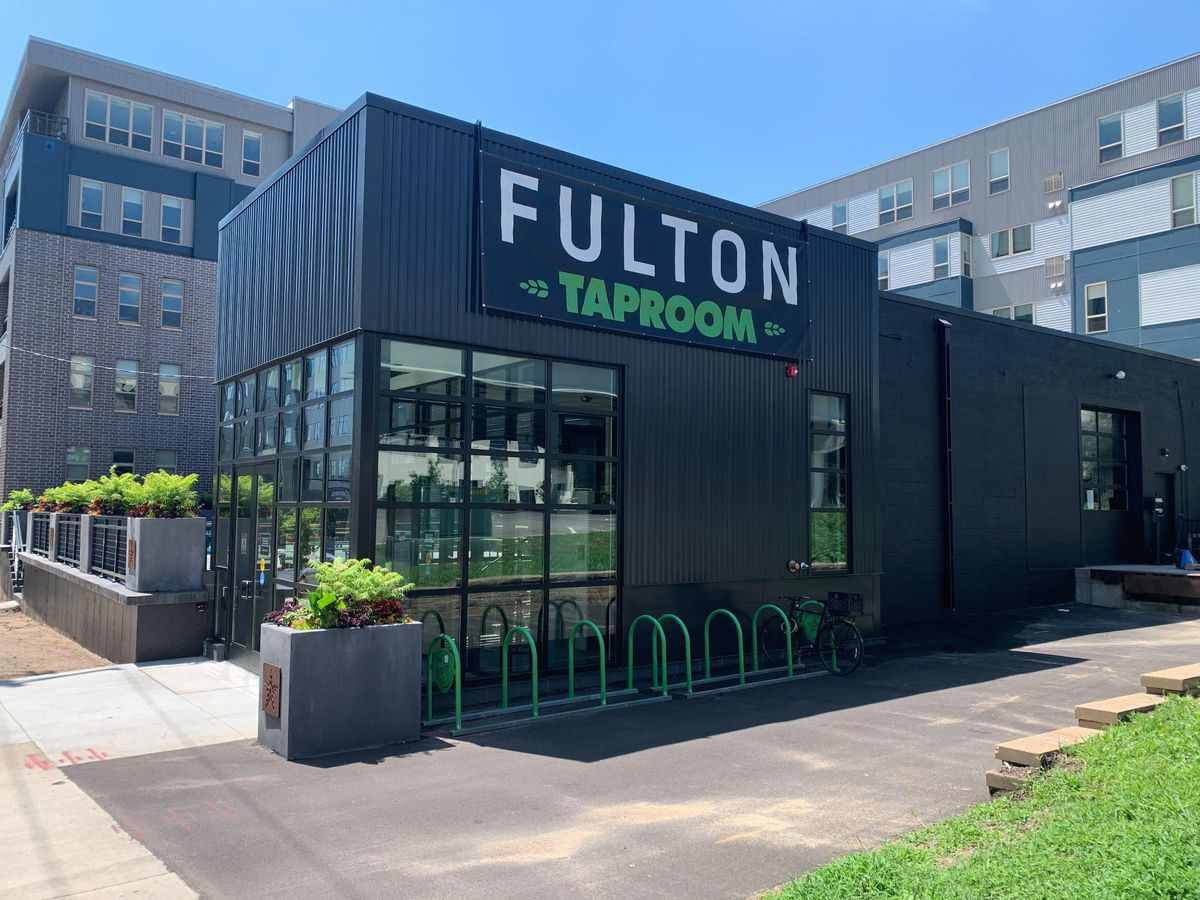 The black exterior building with bright green bike racks, and corner windows.