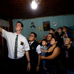 Elders Tanner McKee and Pedro Cabral, missionaries for The Church of Jesus Christ of Latter-day Saints, take a selfie with the Almeida family after teaching a lesson about the church in their home in Paranaguá, Brazil, on Saturday, June 1, 2019.