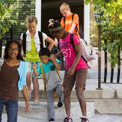 Olivia, 12, Malia, 8, Niya, 12, and Clayson, 10, head to school. Hyrum, 6, decided he wanted to join them so he put on a backpack and walked to the end of the driveway and back. The Walkers say their children all get along well.