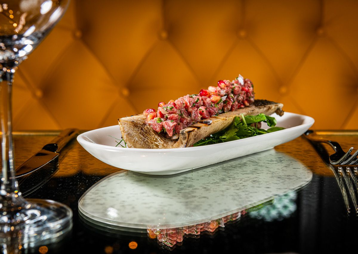A lengthy bone marrow order comes topped with steak tartare.