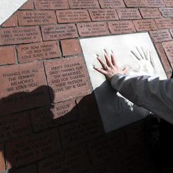 A fan compares her hand to the imprinted hand of former Boston Red Sox third baseman Wade Boggs on a new brick walkway at Fenway Park in Boston Monday, April 9, 2012. The Boston Red Sox baseball home opener is Friday, April 13, 2012.