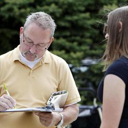In this Sept. 9, 2011, photo, Mellissa Brown, right, a volunteer for Organizing for America, collects a signature from David Koscielak, left, of Hilliard, Ohio, for a petition in a ballot repeal effort by opponents of the Ohio's new elections law, in Columbus, Ohio. After years of expanding when and how people can vote, state legislatures now under new Republican control are moving to trim early voting days, beef up identification requirements and put new restrictions on how voters are notified about absentee ballots.