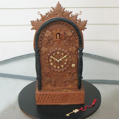 Gingerbread clock showing that it is 10:10 with a small golden key sitting in front of it.