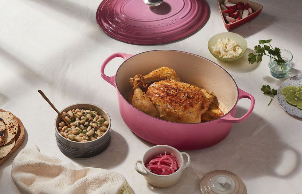 Pink Le Creuset Dutch oven sitting open on a stylish table with a roast chicken inside