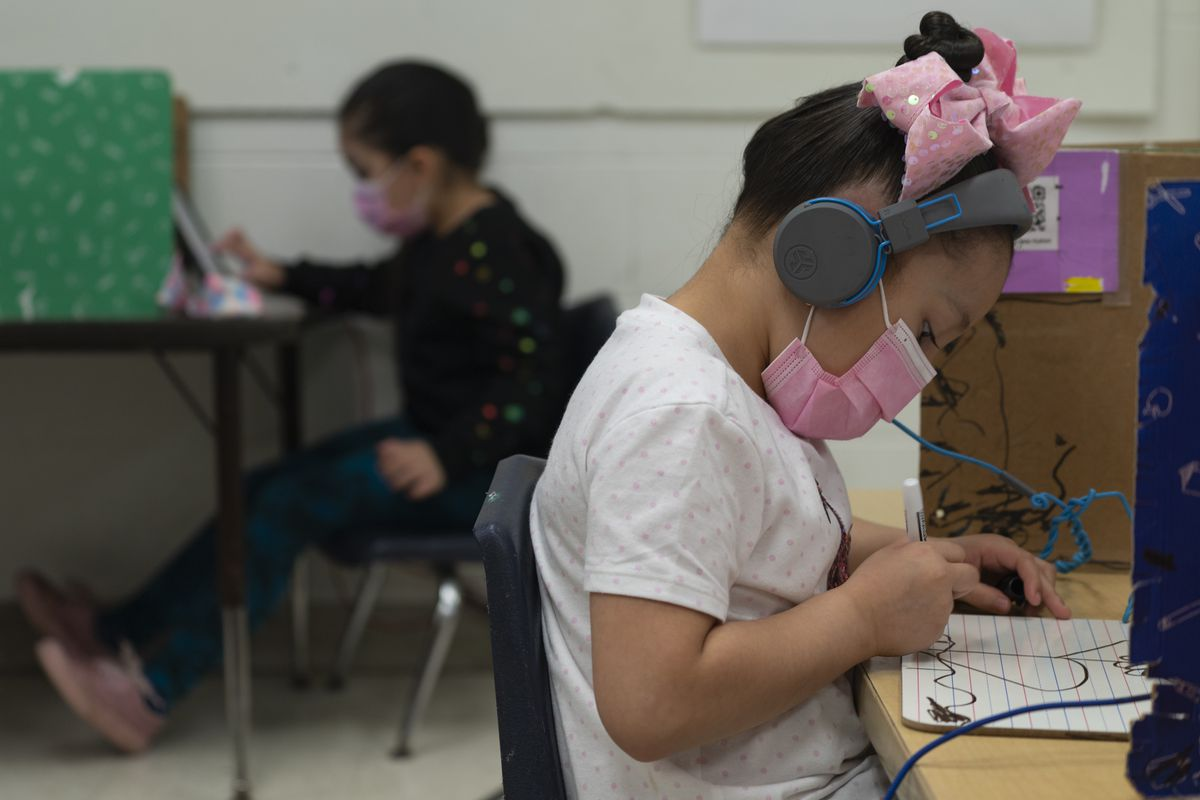 A student wearing a pink bow and protective mask draws on a whiteboard at her desk.