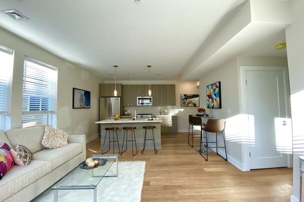 A long living room-dining room area leading to an open kitchen with stools in front of the kitchen's island.