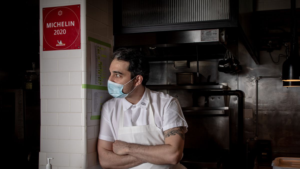 A chef looks around the corner where a Michelin star plaque is hanging