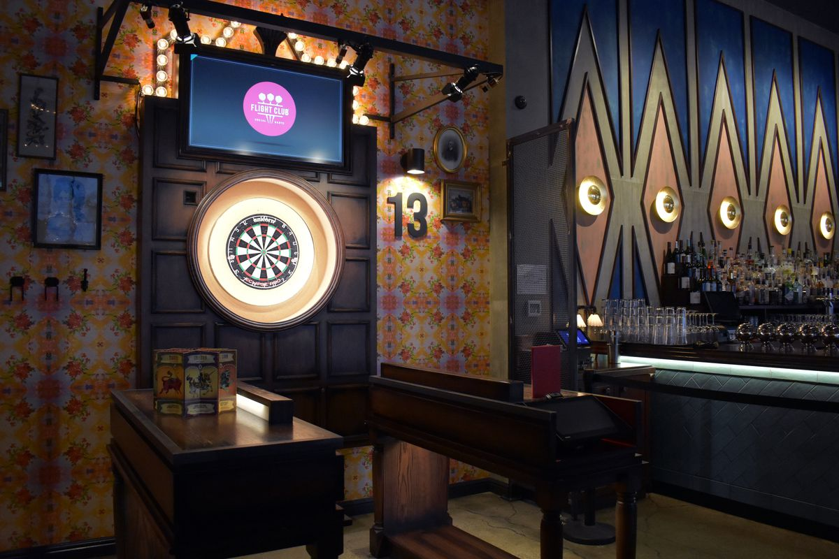 Inside Flight Club's Chicago location, a glowing dart board is visible, with a bar off to the side