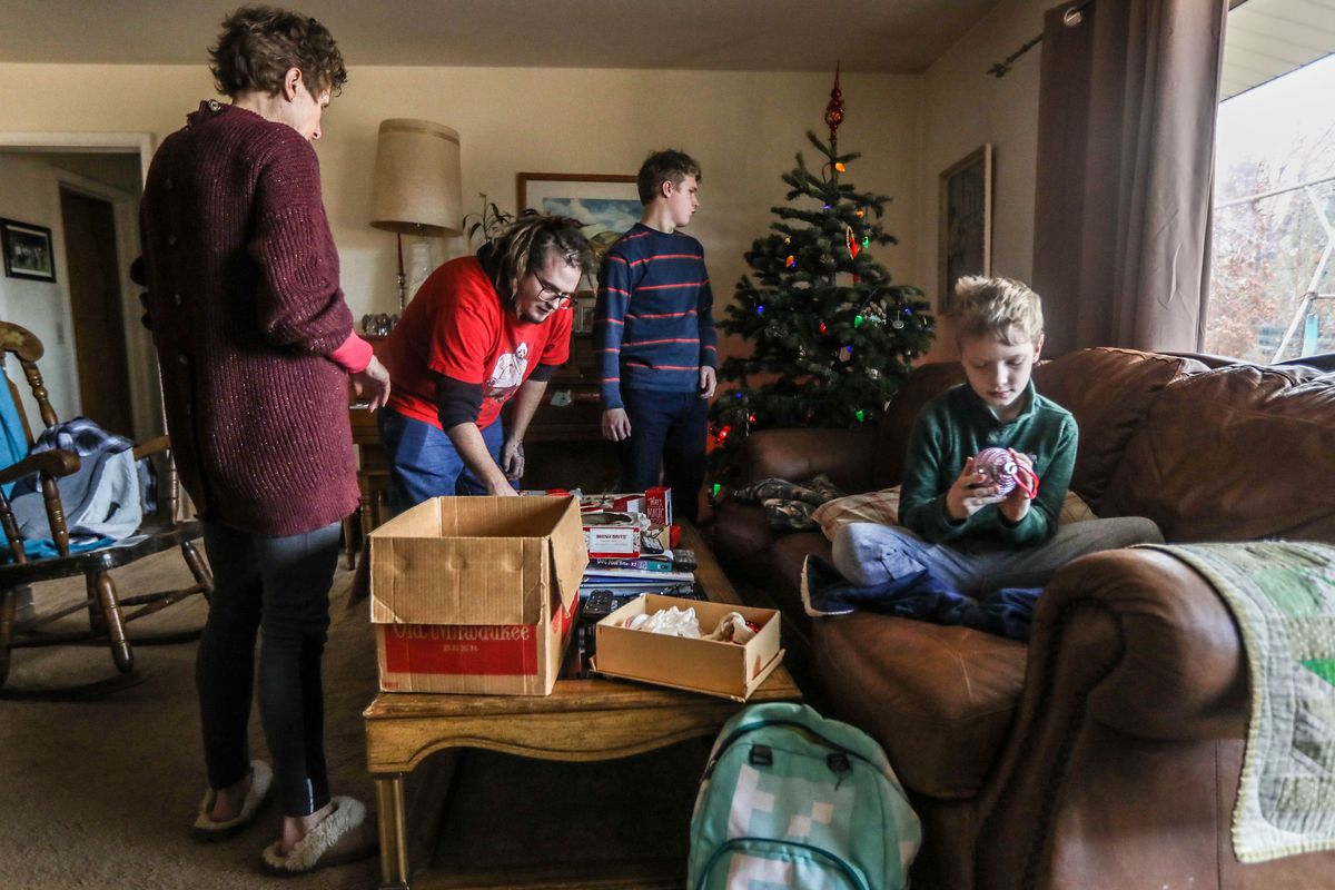 The Straleys remove ornaments from their tree at their home in Salt Lake City on Saturday, Jan. 9, 2020.